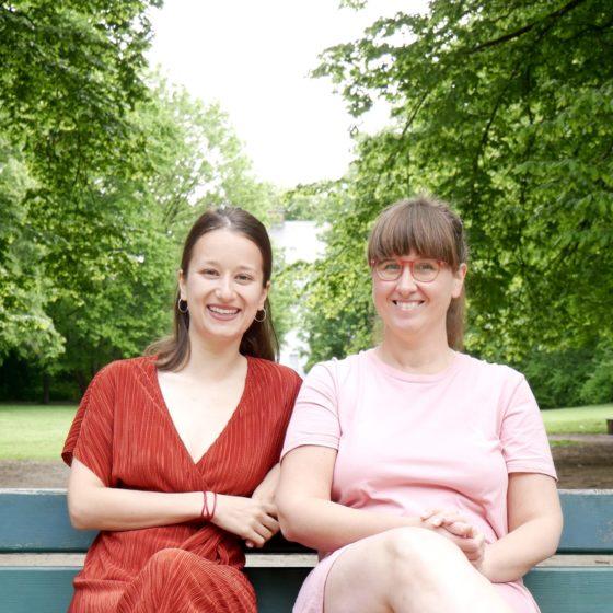 zwei Frauen sitzen auf einer bank